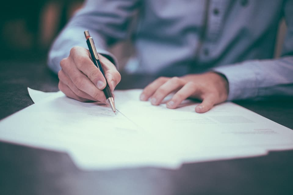 man signing papers with pen