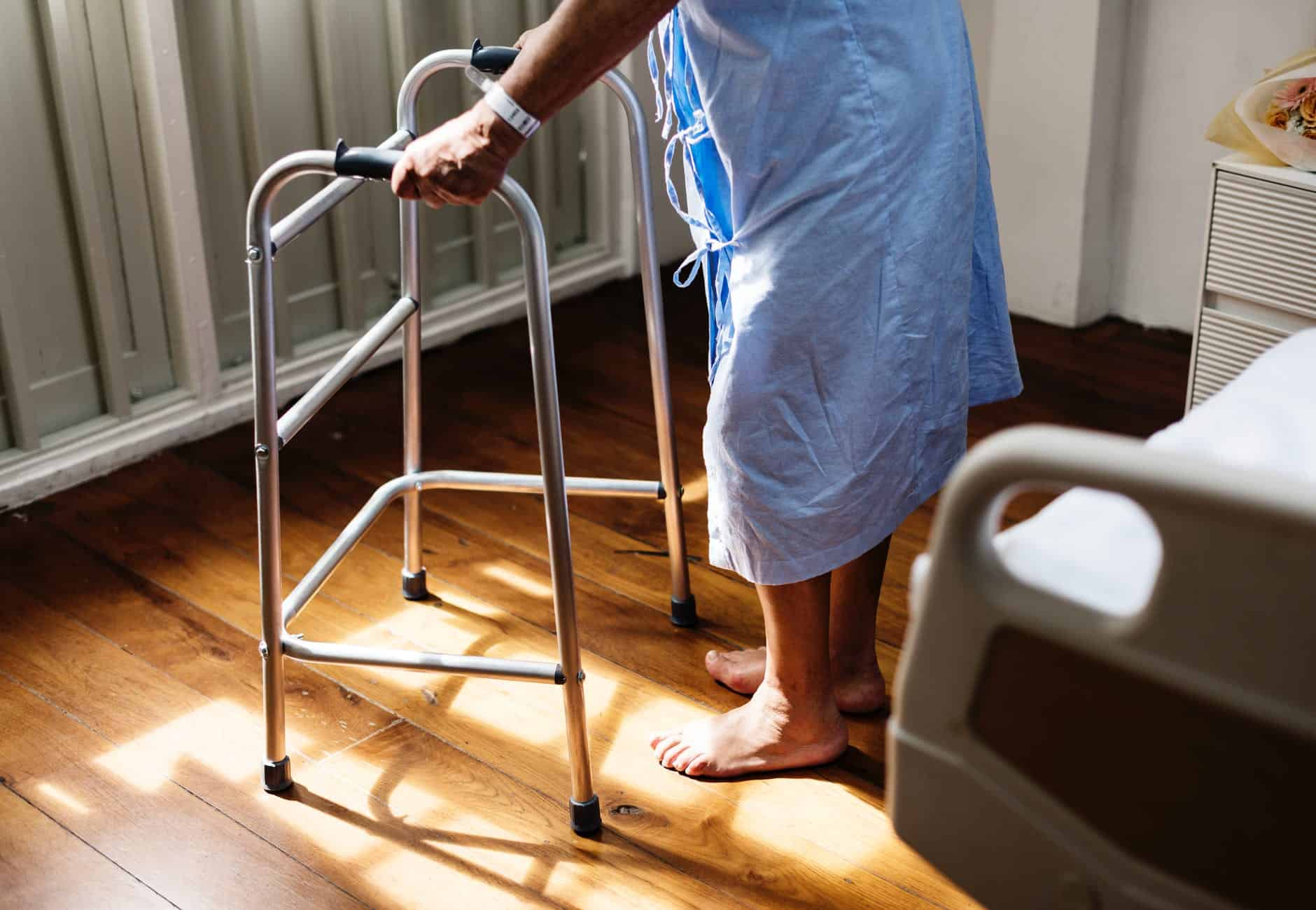 Older man in hospital gown with walker