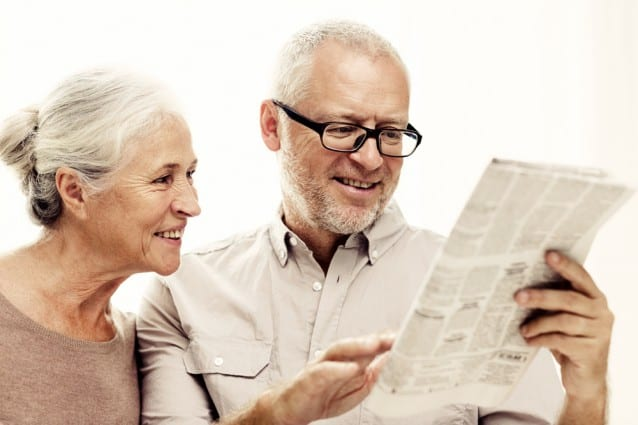 A retired couple reading the newspaper