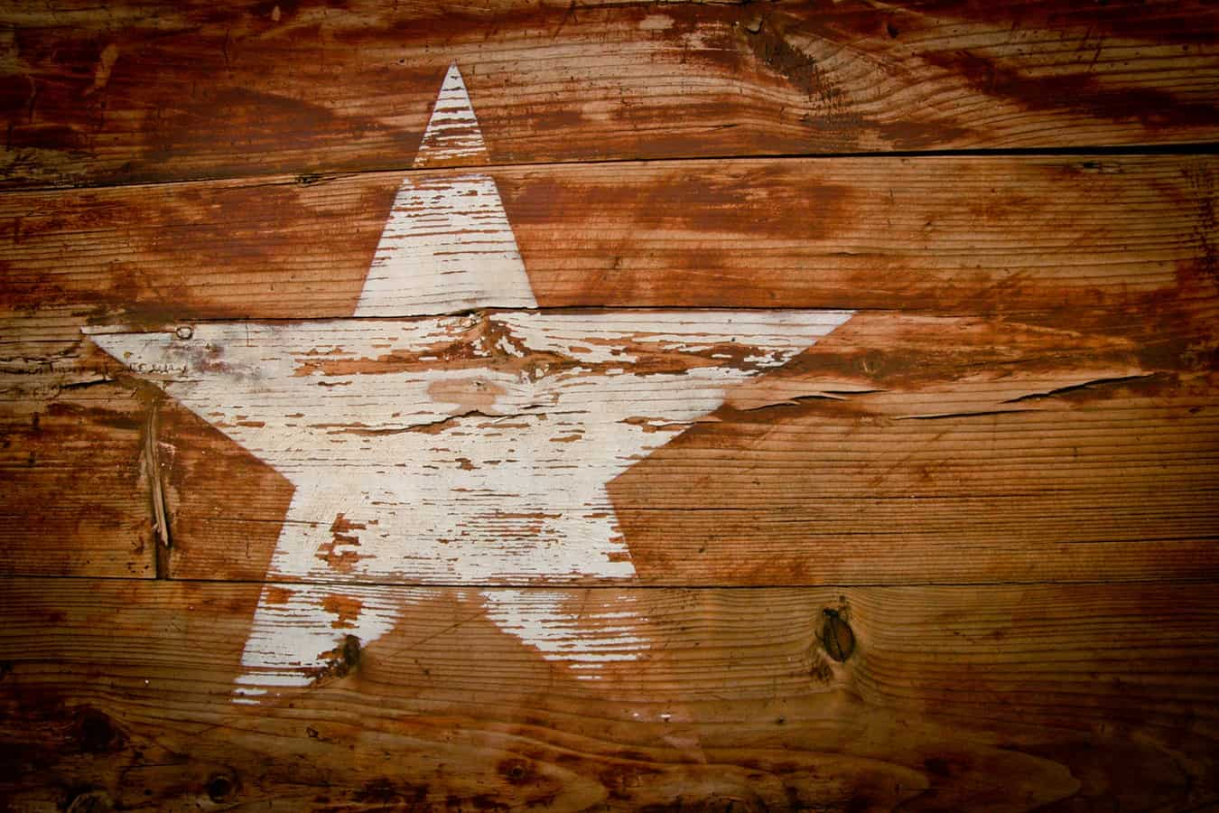 Faded white painted star on wood