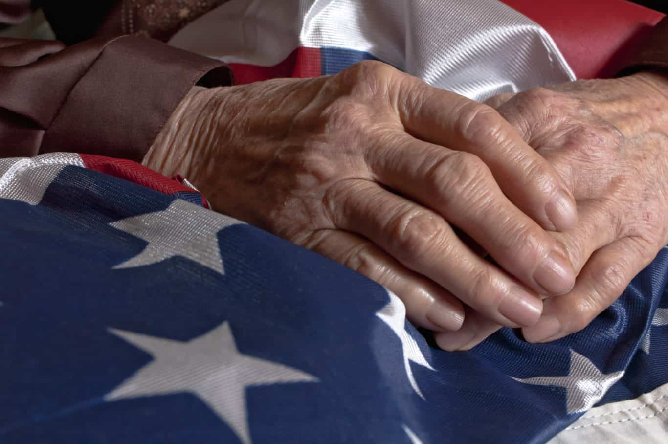Elder's hands over an American flag