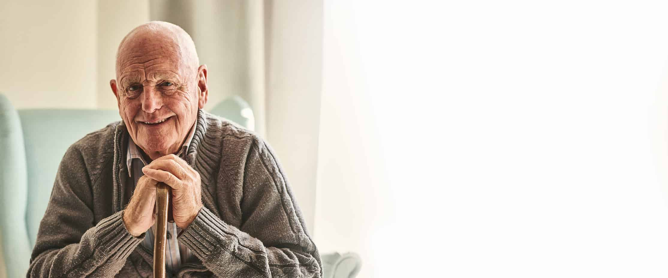 Elderly Man Sitting Down Happy with Care Smiling - Header Image