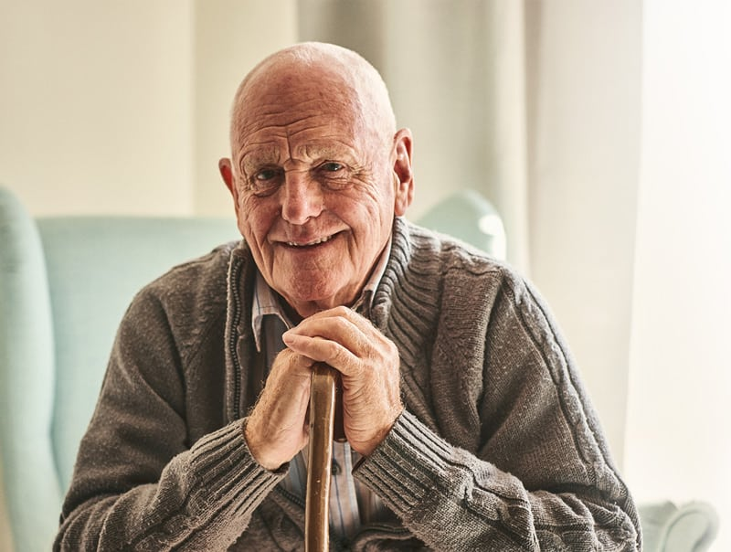Elderly Man Sitting Down Happy with Care Smiling