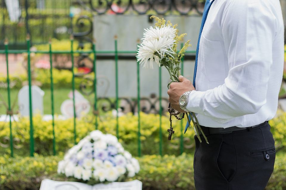 Man with flowers at grave