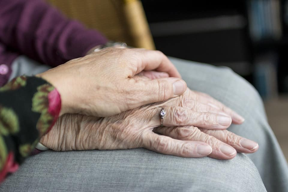 elderly couple's hands on lap