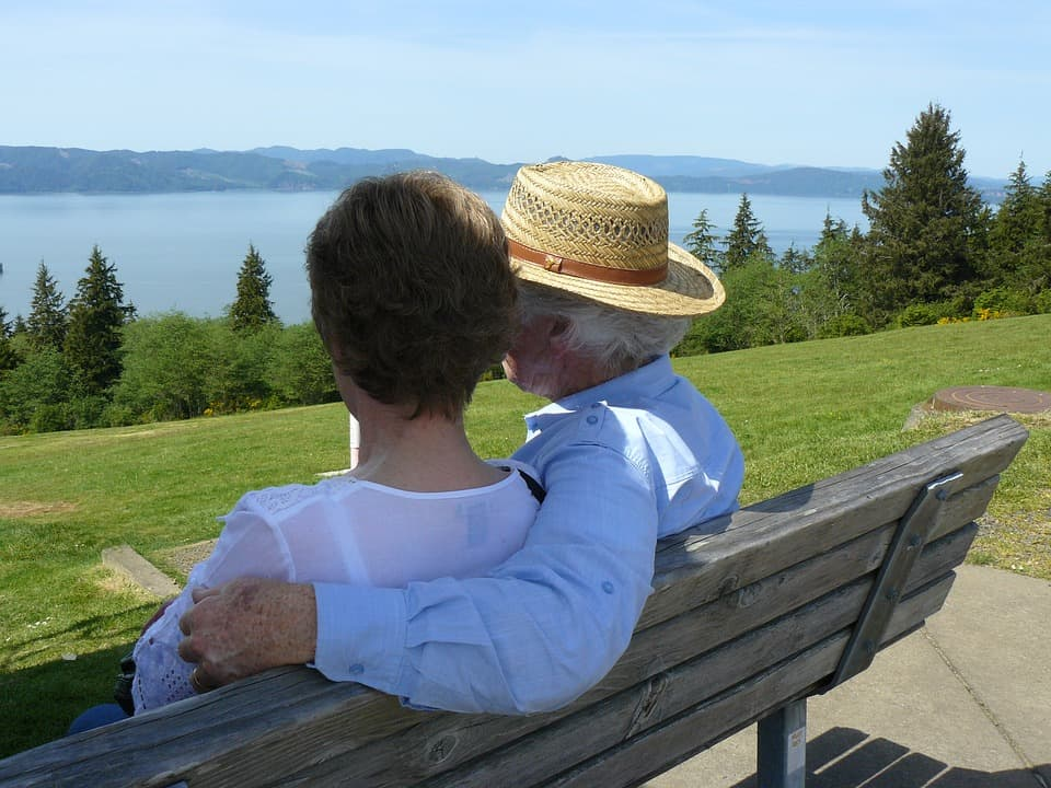 couple sitting on bench looking out over lake