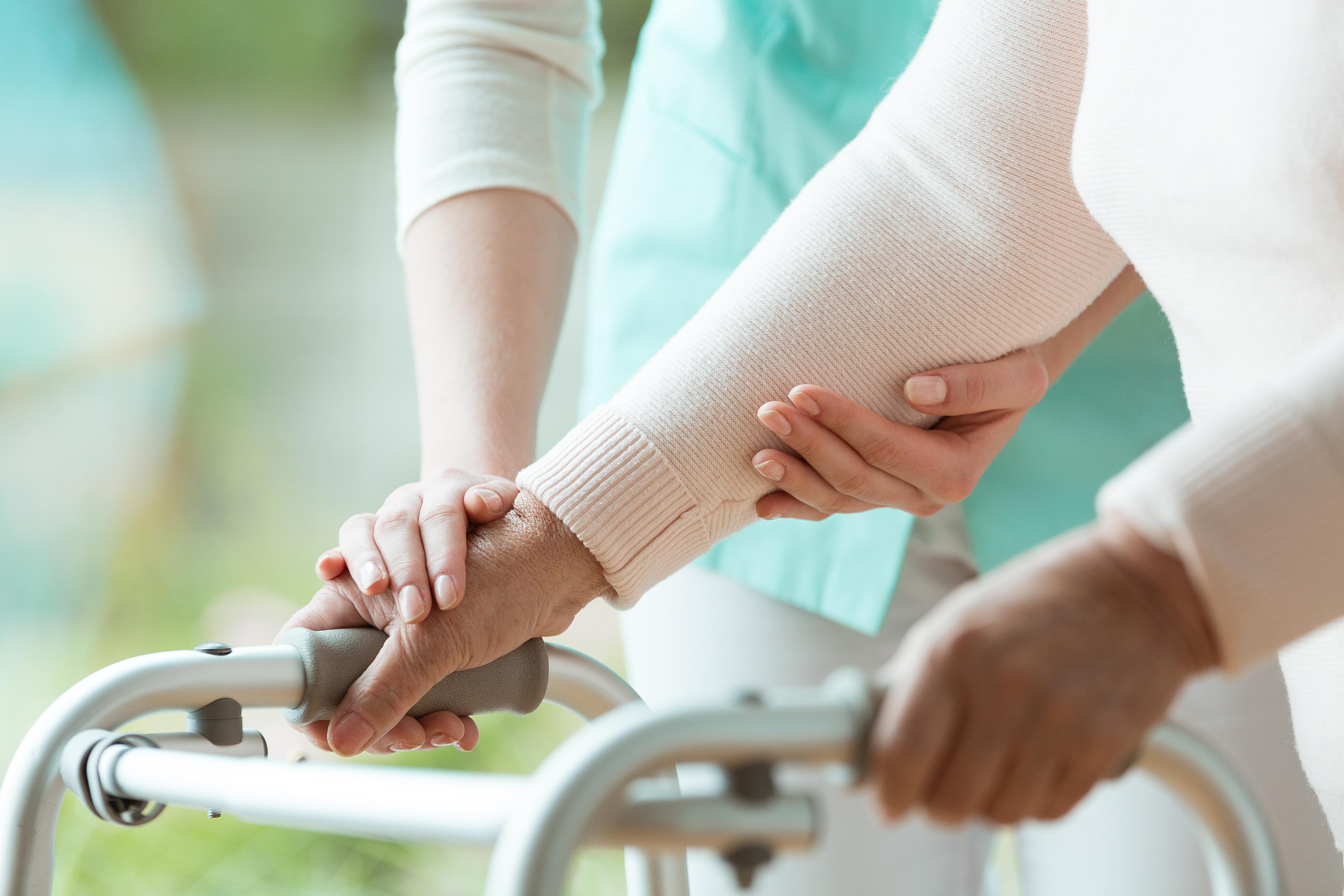 nurse helping elderly woman with metal walker