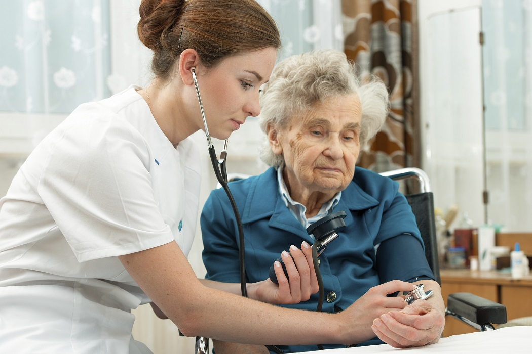 nurse measuring blood pressure of nursing home resident