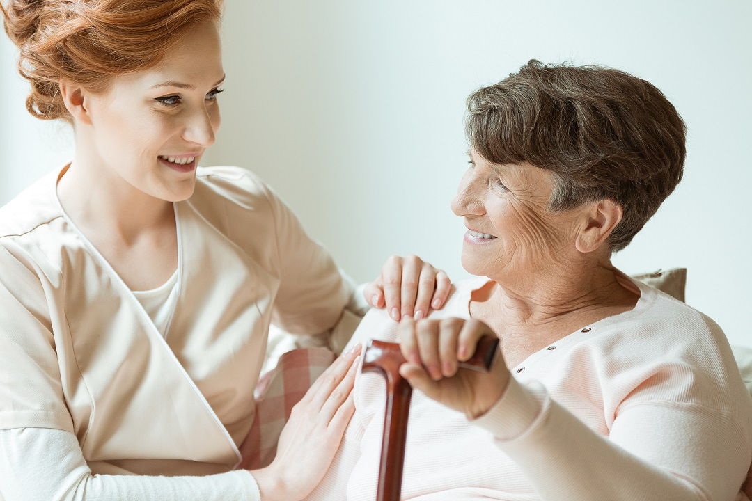 assisted living caregiver helping elderly woman
