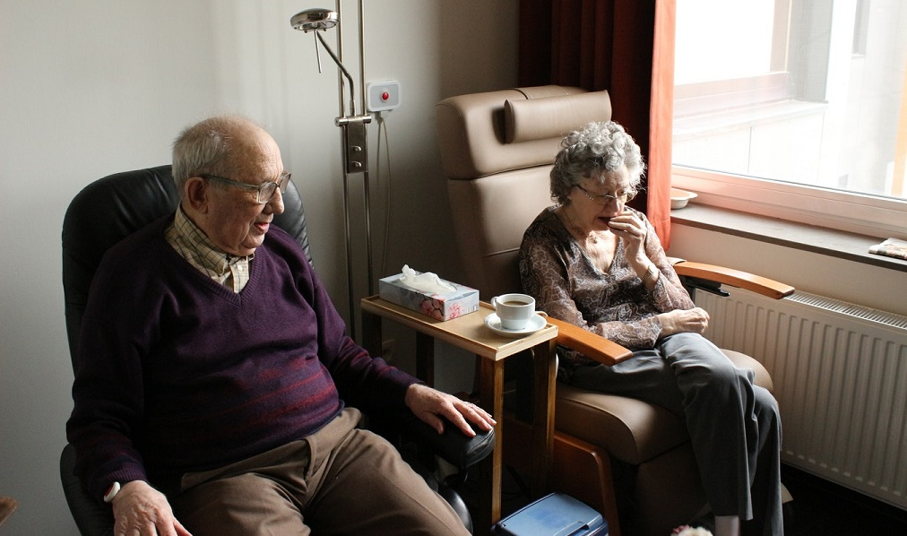 elderly couple sitting in assisted living unit