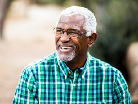 African American man in plaid shirt smiling