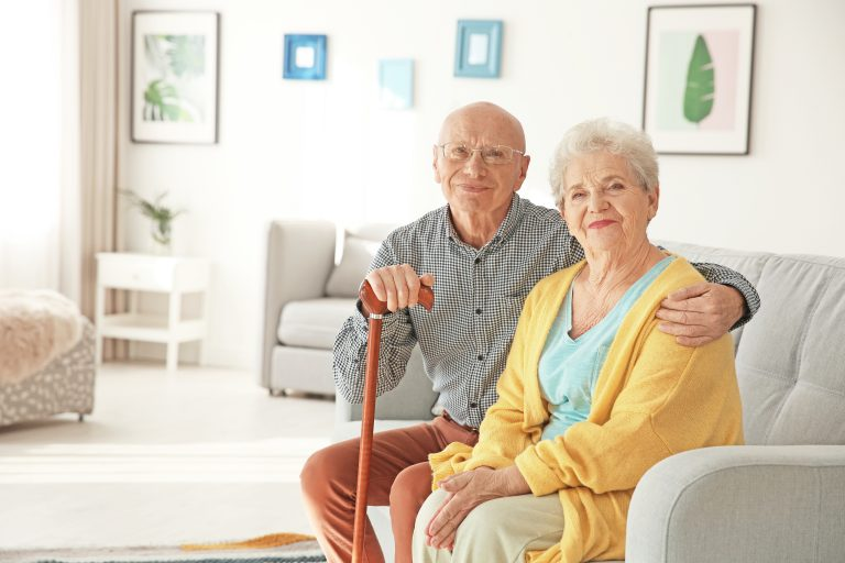 elderly married couple sitting on a couch