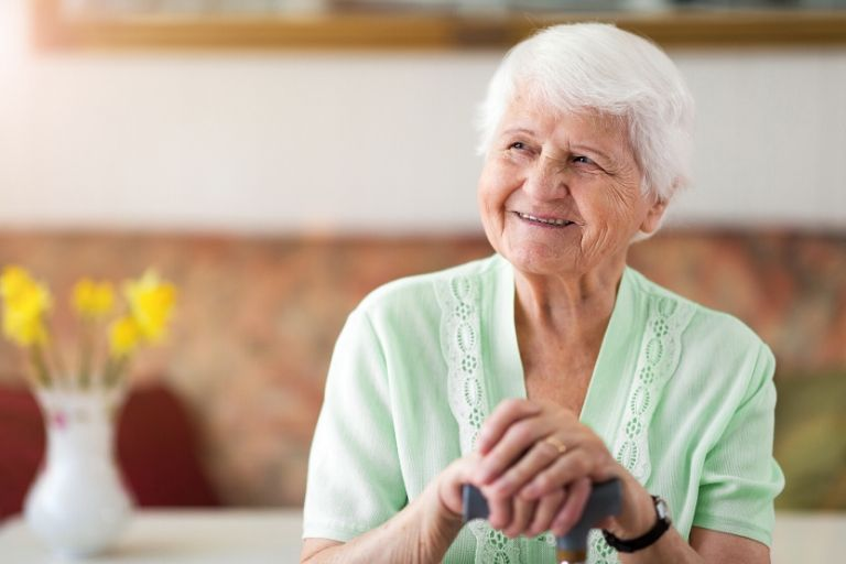 elderly woman in green shirt smiling