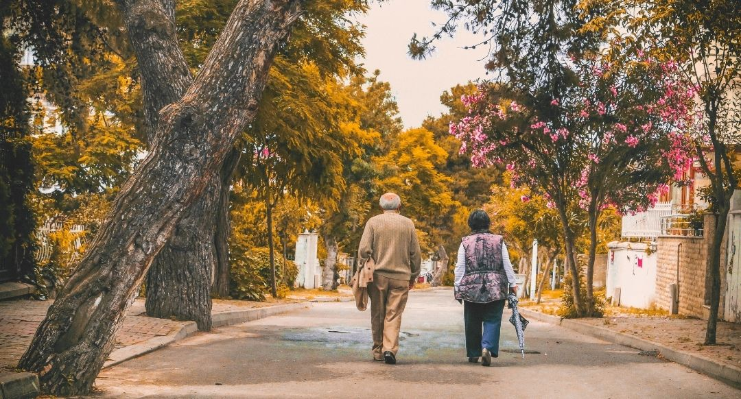 retired elderly couple walking down the street