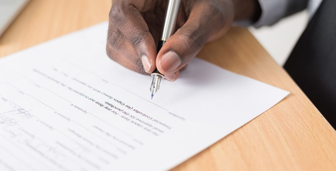 man's hand signing contract document