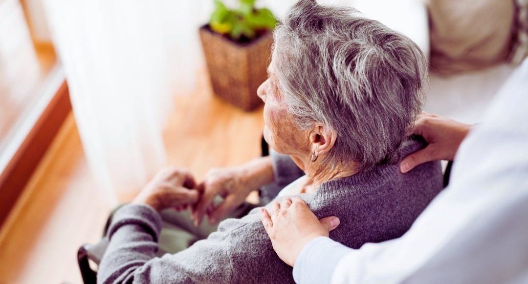 elderly woman in wheel chair with nursing home worker behind her